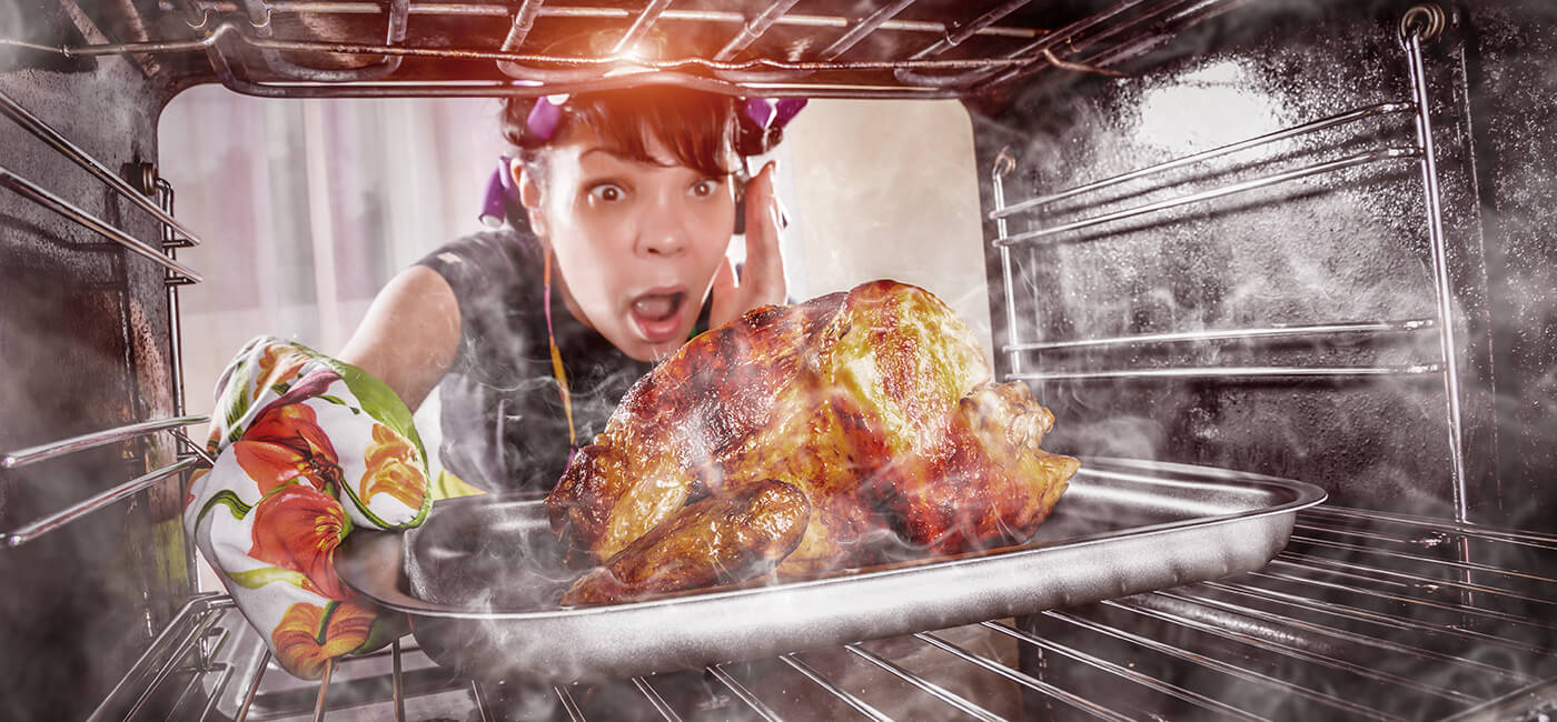 Woman getting turkey out of oven